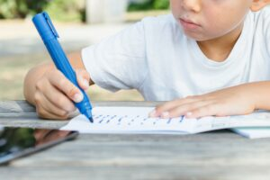 Close-up of kid writing in notepad