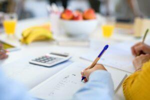 Close-up of homeschooling children studying and writing indoors, coronavirus concept.