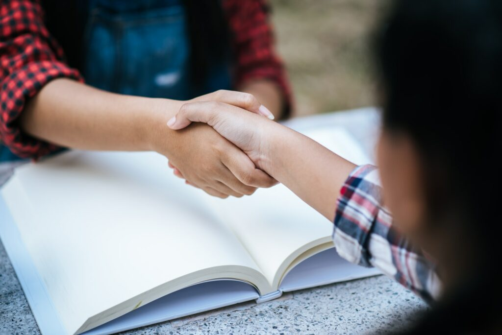 girls college student shake hand her friend at college park