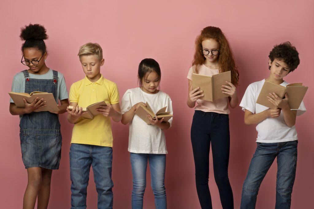 Industrious diverse children reading school textbooks on pink background