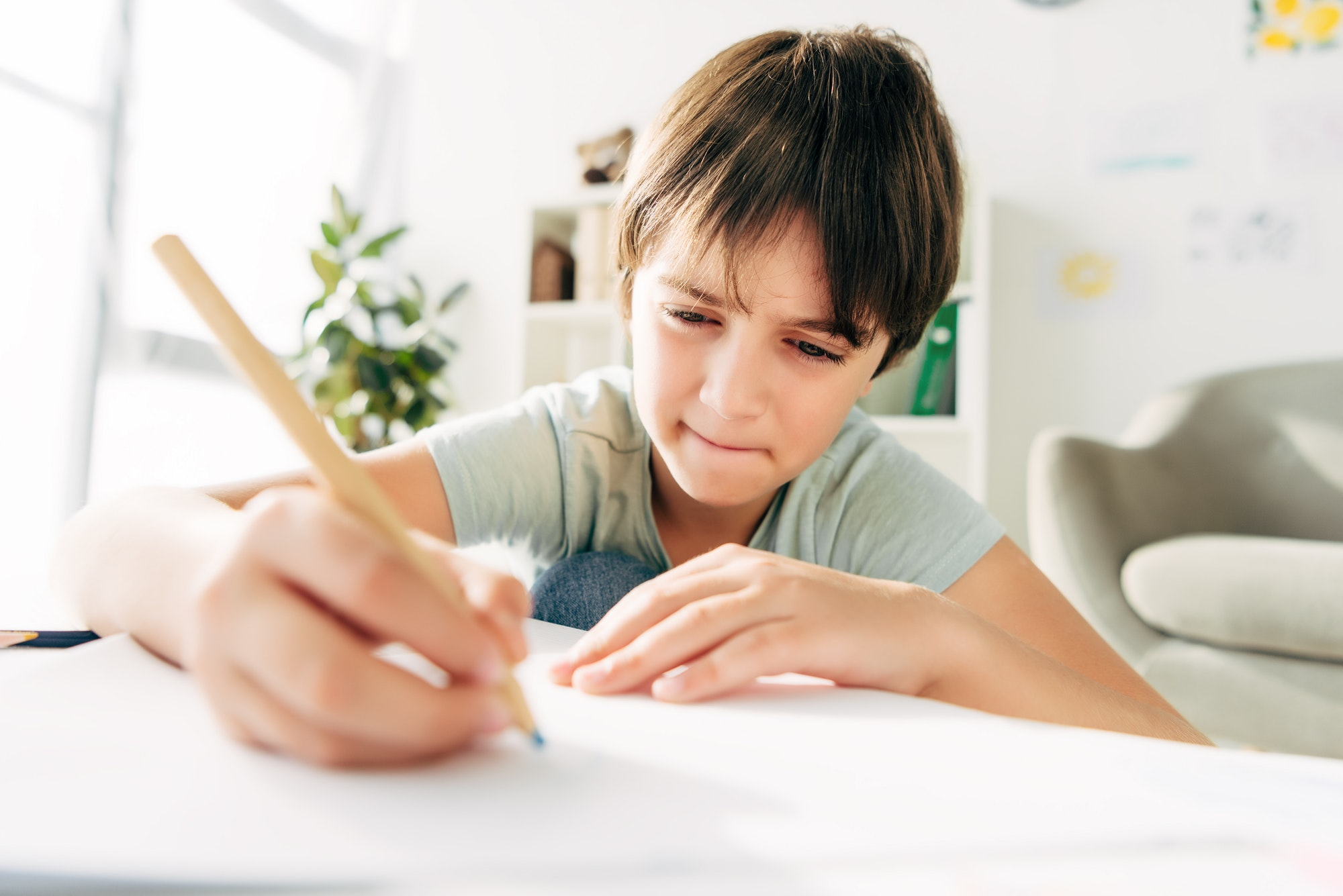 kid with dyslexia drawing with pencil and sitting at table