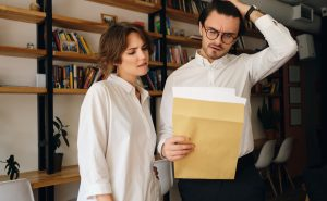 Disappointed business colleagues thoughtfully reading envelope letter working together in office